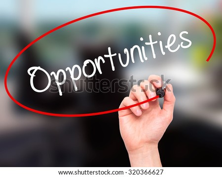 Man Hand writing Opportunities  with black marker on visual screen. Isolated on office. Business, technology, internet concept. - stock photo