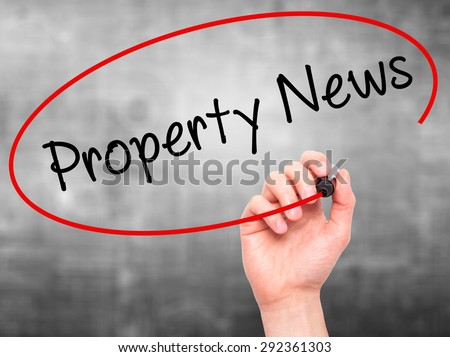 Man Hand writing Property News with black marker on visual screen. Isolated on grey. Business, technology, internet concept. Stock Image - stock photo