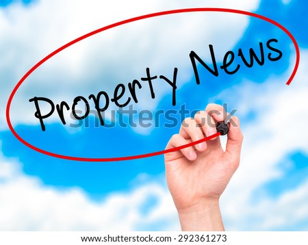 Man Hand writing Property News with black marker on visual screen. Isolated on sky. Business, technology, internet concept. Stock Image - stock photo
