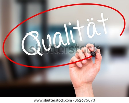 Man Hand writing Quality (Qualitat in German) with black marker on visual screen. Isolated on background. Business, technology, internet concept. Stock Photo - stock photo
