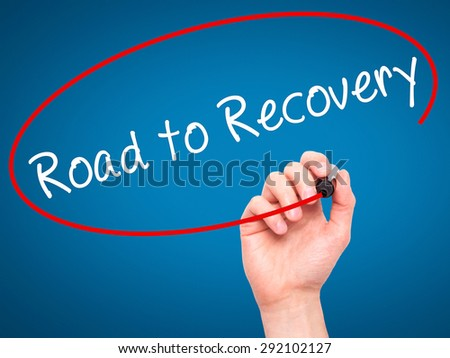 Man Hand writing Road to Recovery with black marker on visual screen. Isolated on blue. Business, technology, internet concept. Stock Image - stock photo