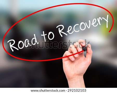 Man Hand writing Road to Recovery with black marker on visual screen. Isolated on office. Business, technology, internet concept. Stock Image - stock photo
