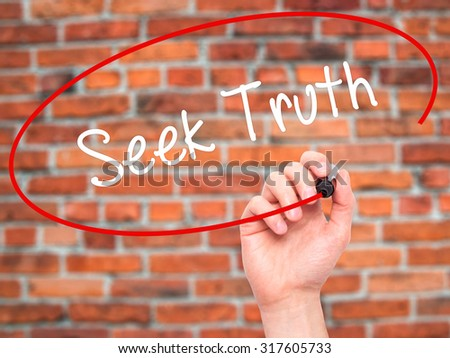 Man Hand writing Seek Truth with black marker on visual screen. Isolated on bricks. Business, technology, internet concept. - stock photo