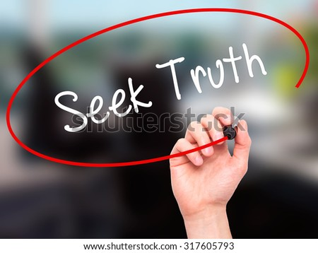 Man Hand writing Seek Truth with black marker on visual screen. Isolated on office. Business, technology, internet concept. - stock photo