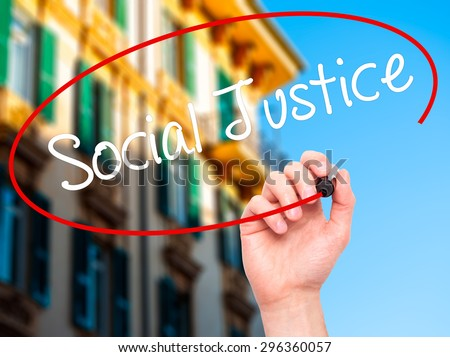 Man Hand writing Social Justice with black marker on visual screen. Isolated on city. Business, technology, internet concept. Stock Photo - stock photo