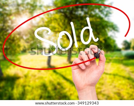 Man Hand writing Sold with black marker on visual screen. Isolated on background. Business, technology, internet concept. Stock Photo - stock photo