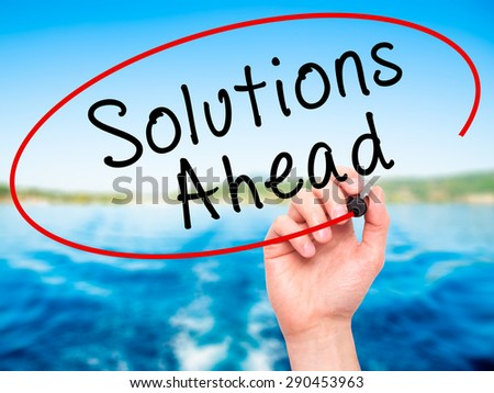 Man Hand writing Solutions Ahead with black marker on visual screen. Isolated on nature. Learn, technology, internet concept. Stock Image - stock photo