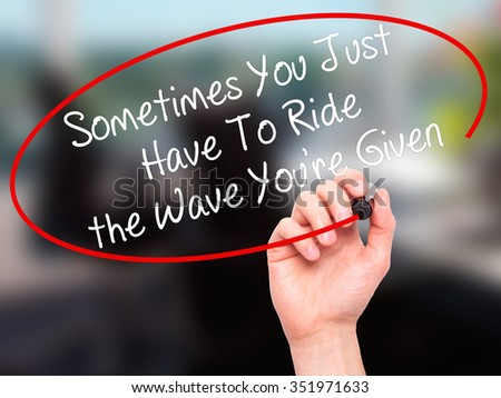 Man Hand writing Sometimes You Just Have To Ride the Wave You're Given with black marker on visual screen. Isolated on background. Business, technology, internet concept. Stock Photo  - stock photo