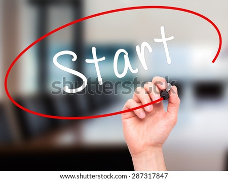 Man Hand writing Start with marker on transparent wipe board. Isolated on office. Business, internet, technology concept. Stock Photo - stock photo