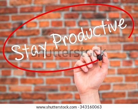 Man Hand writing Stay Productive with black marker on visual screen. Isolated on bricks. Business, technology, internet concept. Stock Photo - stock photo