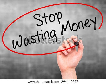 Man Hand writing Stop Wasting Money with black marker on visual screen. Isolated on grey. Business, technology, internet concept. Stock Photo - stock photo