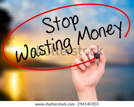 Man Hand writing Stop Wasting Money with black marker on visual screen. Isolated on nature. Business, technology, internet concept. Stock Photo - stock photo