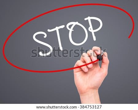 Man Hand writing STOP  with black marker on visual screen. Isolated on background. Business, technology, internet concept. Stock Photo - stock photo