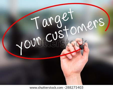 Man Hand writing Target your customers with black marker on visual screen. Isolated on office. Business, technology, internet concept. Stock Image - stock photo