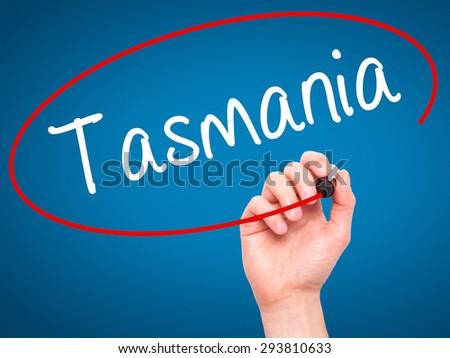 Man Hand writing Tasmania with black marker on visual screen. Isolated on blue. Business, technology, internet concept. Stock Photo - stock photo
