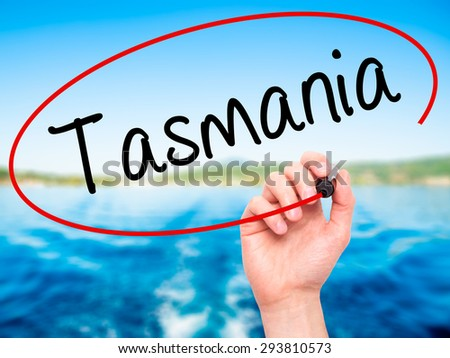 Man Hand writing Tasmania with black marker on visual screen. Isolated on nature. Business, technology, internet concept. Stock Photo - stock photo