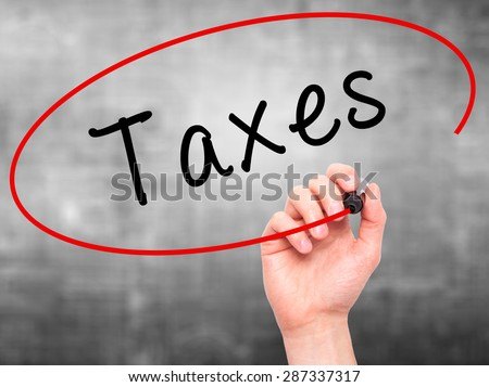 Man Hand writing Taxes with marker on transparent wipe board. Isolated on grey. Business, internet, technology concept. Stock Photo - stock photo