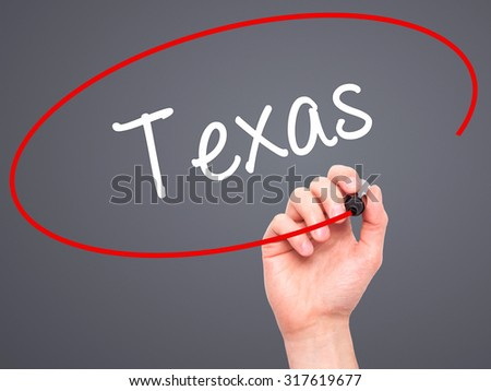 Man Hand writing Texas  with black marker on visual screen. Isolated on grey. Business, technology, internet concept. - stock photo
