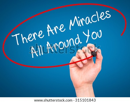 Man Hand writing There Are Miracles All Around You  with black marker on visual screen. Isolated on blue. Business, technology, internet concept. Stock Photo - stock photo