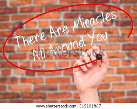 Man Hand writing There Are Miracles All Around You  with black marker on visual screen. Isolated on bricks. Business, technology, internet concept. Stock Photo - stock photo