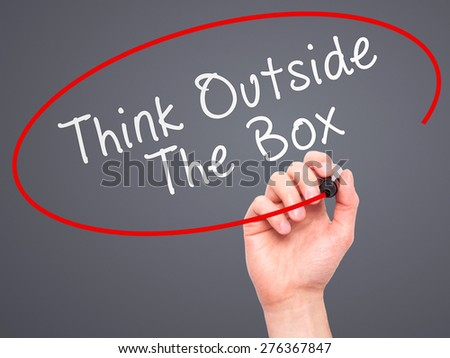 Man Hand writing Think Outside The Box with marker on transparent wipe board. Isolated on grey. Business, internet, technology concept.  Stock Photo - stock photo