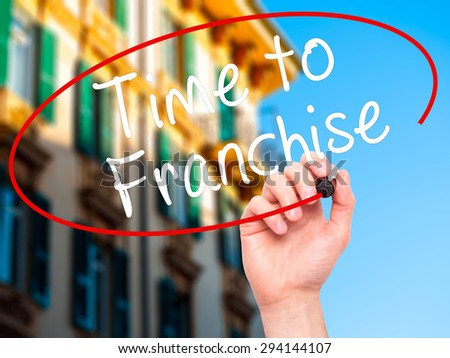 Man Hand writing Time to Franchise with black marker on visual screen. Isolated on city. Business, technology, internet concept. Stock Photo - stock photo