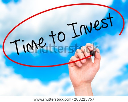 Man Hand writing Time to Invest with marker on transparent wipe board. Isolated on sky. Business, internet, technology concept. Stock Photo - stock photo