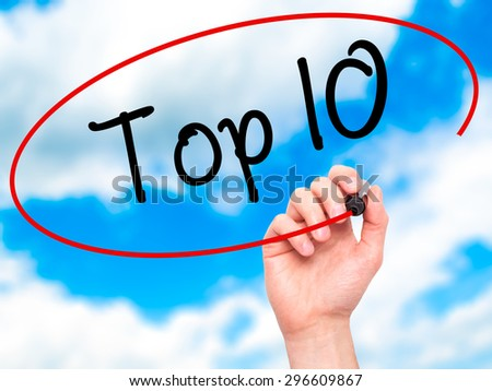Man Hand writing Top 10 with black marker on visual screen. Isolated on sky. Business, technology, internet concept. Stock Photo - stock photo