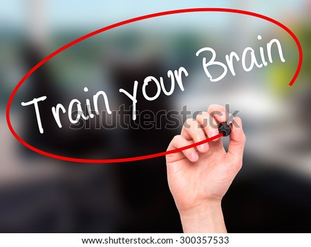 Man Hand writing Train your Brain with black marker on visual screen. Isolated on office. Business, technology, internet concept. Stock Photo - stock photo