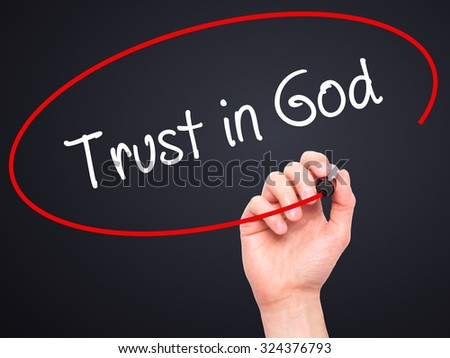 Man Hand writing Trust in God with black marker on visual screen. Isolated on black. Business, technology, internet concept. Stock Photo - stock photo