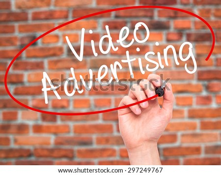 Man Hand writing Video Advertising with black marker on visual screen. Isolated on bricks. Business, technology, internet concept. Stock Photo - stock photo