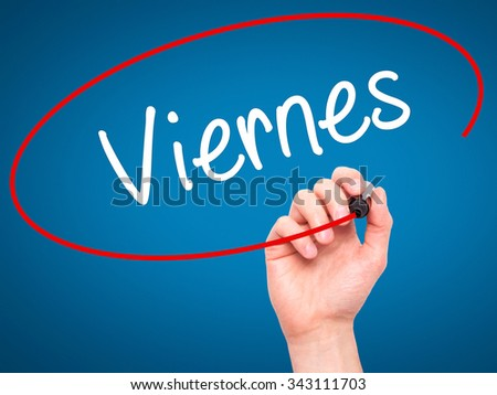 Man Hand writing Viernes (Friday in Spanish) with black marker on visual screen. Isolated on blue. Business, technology, internet concept. Stock Photo - stock photo