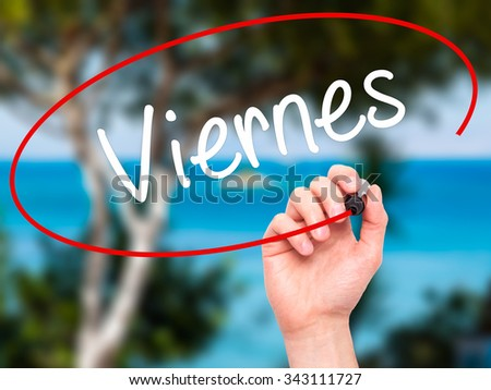 Man Hand writing Viernes (Friday in Spanish) with black marker on visual screen. Isolated on nature. Business, technology, internet concept. Stock Photo - stock photo