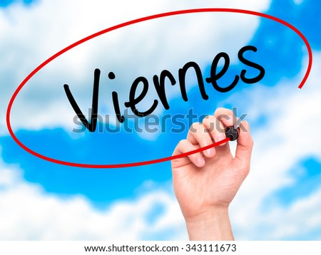 Man Hand writing Viernes (Friday in Spanish) with black marker on visual screen. Isolated on sky. Business, technology, internet concept. Stock Photo - stock photo