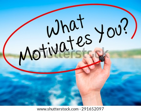 Man Hand writing What Motivates You? with black marker on visual screen. Isolated on nature. Business, technology, internet concept. Stock Image - stock photo