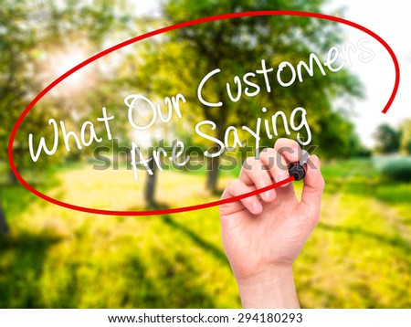 Man Hand writing What Our Customers Are Saying with black marker on visual screen. Isolated on nature. Business, technology, internet concept. Stock Photo - stock photo