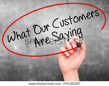 Man Hand writing What Our Customers Are Saying with black marker on visual screen. Isolated on grey. Business, technology, internet concept. Stock Photo - stock photo