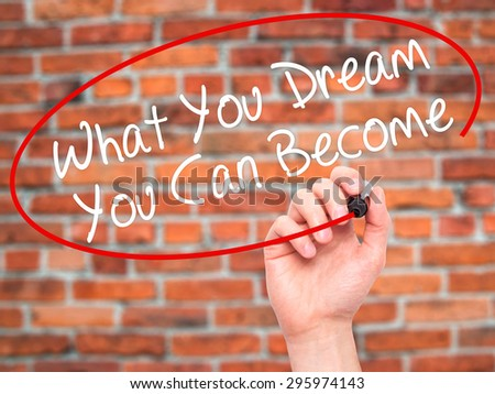 Man Hand writing What You Dream You Can Become with black marker on visual screen. Isolated on bricks. Business, technology, internet concept. Stock Photo - stock photo