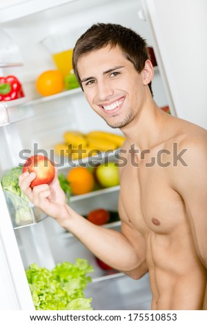 Man hands apple standing near the opened fridge. Concept of healthy and dieting food - stock photo