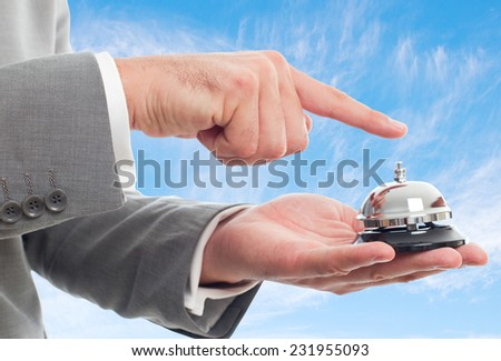 Man hands close up with grey suit over clouds background. Pushing a hotel bell - stock photo