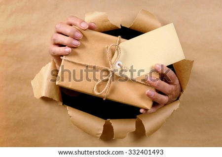 Man hands delivering or receiving parcel box through torn brown paper background - stock photo