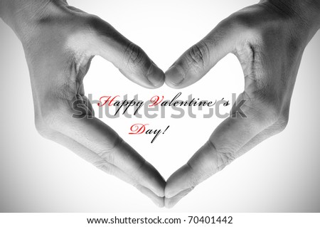 man hands forming a heart and the sentence happy valentines day - stock photo