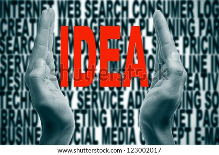 man hands forming brackets and the word idea written in red inside, on a background full of words about internet concept - stock photo