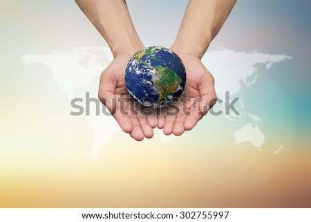 man hands hold the world on blurred map over warm tone colorful sky background:safe healing planet.Global carbon emissions:earth day concept:love protection:Elements of this image furnished by NASA. - stock photo