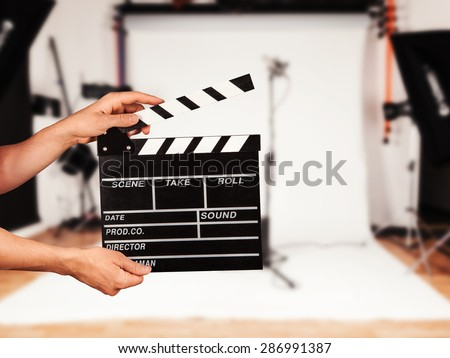 Man hands holding film clapper. Blur film studio on background - stock photo