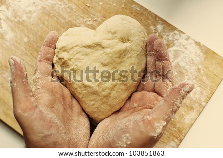 Man hands holding homemade heart shaped pastry on a wooden board - stock photo