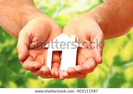 Man hands holding paper house - stock photo