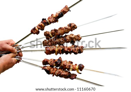 man hands holding roasted shish kebab on skewers in a semicircle - stock photo