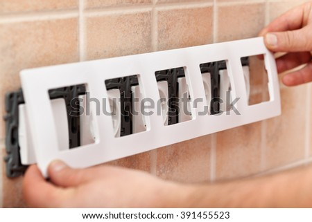 Man hands installing decorative mask onto electrical wall fixture - closeup - stock photo