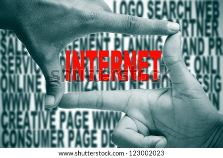 man hands making a frame with its fingers and the word internet written in red inside, on a background full of words about internet concept - stock photo